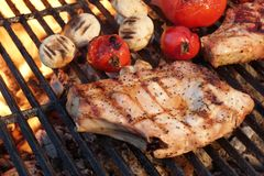 Pork Rib Steaks, Tomato And Mushrooms On Hot BBQ Grill Royalty Free Stock Image
