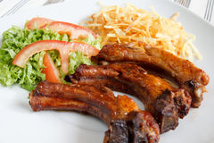 Pork ribs. French fries and fresh salad stock photos