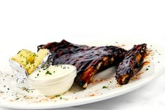 Pork ribs with a baked potato and sour cream Royalty Free Stock Image