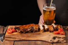 Pork ribs in barbecue sauce and honey baked tomatoes on the old wooden table. Meats and light beer on black background with copy s. Pace. In the background a man Stock Image