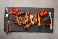 Pork ribs in barbecue sauce and honey roasted tomatoes on a black slate dish. A great snack to beer on a light stone table. Top vi Royalty Free Stock Photos