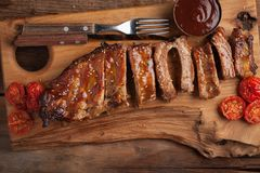 Pork ribs in barbecue sauce and honey roasted tomatoes on a wooden board. A great snack to beer on a rustic wooden table. Top view.  royalty free stock photography