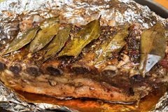 Pork ribs. Barbecued grilled ribs seasoned with hot spices and laurel leaves laying on a folio close up Royalty Free Stock Photography