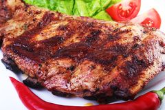 Pork ribs on barbeque and chili pepper with tomato, lettuce leaves on white plate.  royalty free stock photo