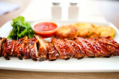 Pork ribs and barbeque sauce with parsley and bread. Main dish - pork ribs and barbeque sauce with parsley and bread stock photo