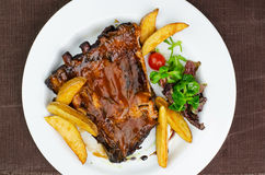 Pork Ribs With BBQ Sauce. And Fried Potatoes On White Plate Shot From Above stock images