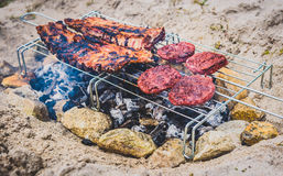 Pork ribs and burgers on homemade improvised BBQ barbecue grill. Stock Photo