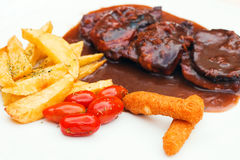 Pork ribs and chicken fingers with bbq sauce and a side of fries and cherry tomatoes Royalty Free Stock Images