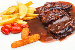 Pork ribs and chicken fingers with bbq sauce and a side of fries and cherry tomatoes Stock Images