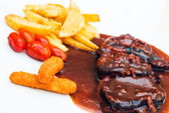 Pork ribs and chicken fingers with bbq sauce and a side of fries and cherry tomatoes Stock Photography
