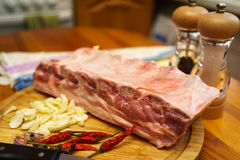 Pork ribs. Fresh pork ribs, meat marinated and prepared for roast with garlic. Laying on a wooden table on a round cutting board with knife, chilly peppers and Royalty Free Stock Photography