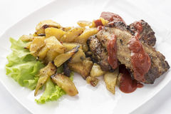 Pork ribs with fried potatoes. Stock Photography