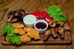 Pork ribs with honey sauce, spicy chicken wings, grilled peppers Royalty Free Stock Photo