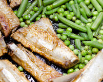 Pork ribs with peas and green beans Stock Photography