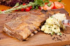Pork ribs with potato salad on wooden cutting board. Close up stock photography