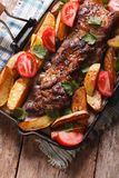 Pork ribs, potatoes close-up on a grill pan. vertical top view Stock Image