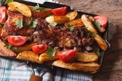 Pork ribs, potatoes and tomatoes closeup. Horizontal top view Stock Photography
