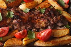 Pork ribs, potatoes and tomatoes macro. horizontal top view Royalty Free Stock Photo