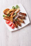 Pork ribs, potatoes and tomatoes on a plate top view vertical Stock Image