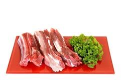 Pork ribs on red plate. White background, studio shot Stock Image