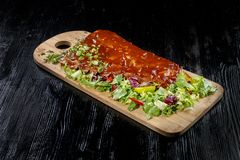 Pork ribs with sauce laid out on a wooden board, stock photography