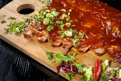 Pork ribs with sauce laid out on a wooden board. stock images