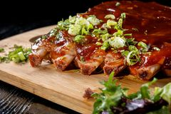 Pork ribs with sauce laid out on a wooden board. royalty free stock photos