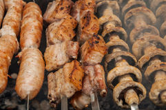 pork ribs, sausages and field mushroom fried on skewers on a brazier Stock Photos