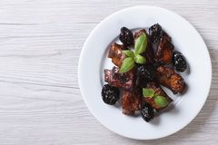 Pork ribs stewed with prunes on a plate. horizontal top view Stock Image
