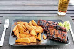 Pork ribs with wedges potatoes on black plate Royalty Free Stock Photos