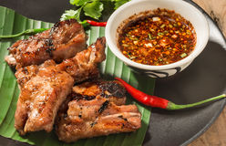 Pork rip grill with garnish on wooden table. Royalty Free Stock Images