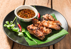 Pork rip grill with garnish on wooden table. Stock Photos