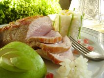 Pork roast. Roast pork served with risotto garnish and decorated with apple and lettuce Stock Image