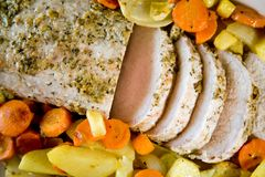 Pork roast. Fresh home made pork roast with some slices served on a plate with vegetables Royalty Free Stock Photography
