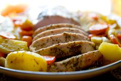 Pork roast. Fresh home made pork roast with some slices served on a plate with vegetables Stock Photo