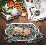 Pork roast in with herbs ,spices and vegetables in roaster dish on wooden rustic kitchen table, top view. Royalty Free Stock Photography