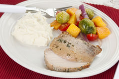 Pork Roast Meal. Baked pork roast garnished with herbs served with brussels sprouts and butternut squash salad and mashed potatoes made with sour cream and Royalty Free Stock Photos