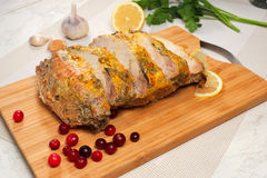 Pork roast with mustard sauce. Sliced piece of pork on a cutting board.beside lemon, garlic and cranberries Stock Photo