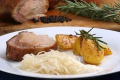 pork with roast potatoes and sauerkraut royalty free stock photos