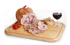 Pork roast. On wooden cupboard with wine and tomatoes Stock Photos