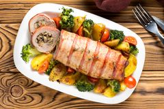 Pork roll wrapped in bacon stuffed with mushrooms and beans, vegetables on the side. Beautiful festive main dish for Christmas. Pork roll wrapped in bacon stock image