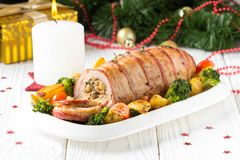 Pork roll wrapped in bacon stuffed with mushrooms and beans, vegetables on the side. Beautiful festive main dish for Christmas. Pork roll wrapped in bacon royalty free stock photography