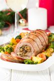Pork roll wrapped in bacon stuffed with mushrooms and beans, vegetables on the side. Beautiful festive main dish for Christmas. Pork roll wrapped in bacon royalty free stock image