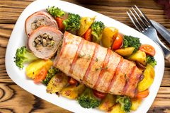 Pork roll wrapped in bacon stuffed with mushrooms and beans, vegetables on the side. Beautiful festive main dish for Christmas. Pork roll wrapped in bacon royalty free stock images