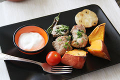 Pork rolls on black plate Stock Images