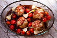Pork rolls with cherry tomatoes and garlic royalty free stock image