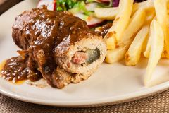Pork roulade with french fries with salad. On a plate Stock Images