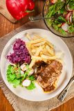 Pork roulade with french fries with salad. On a plate Stock Photography