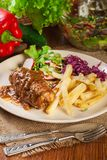 Pork roulade with french fries with salad. On a plate Royalty Free Stock Photo