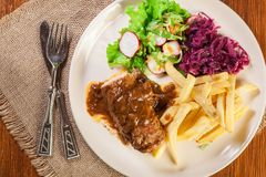 Pork roulade with french fries with salad. On a plate Royalty Free Stock Image